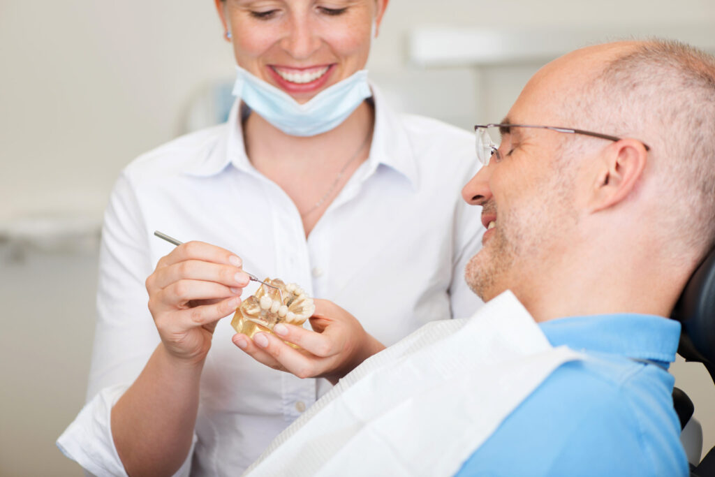 Female dentist explains to patient how dental crowns work