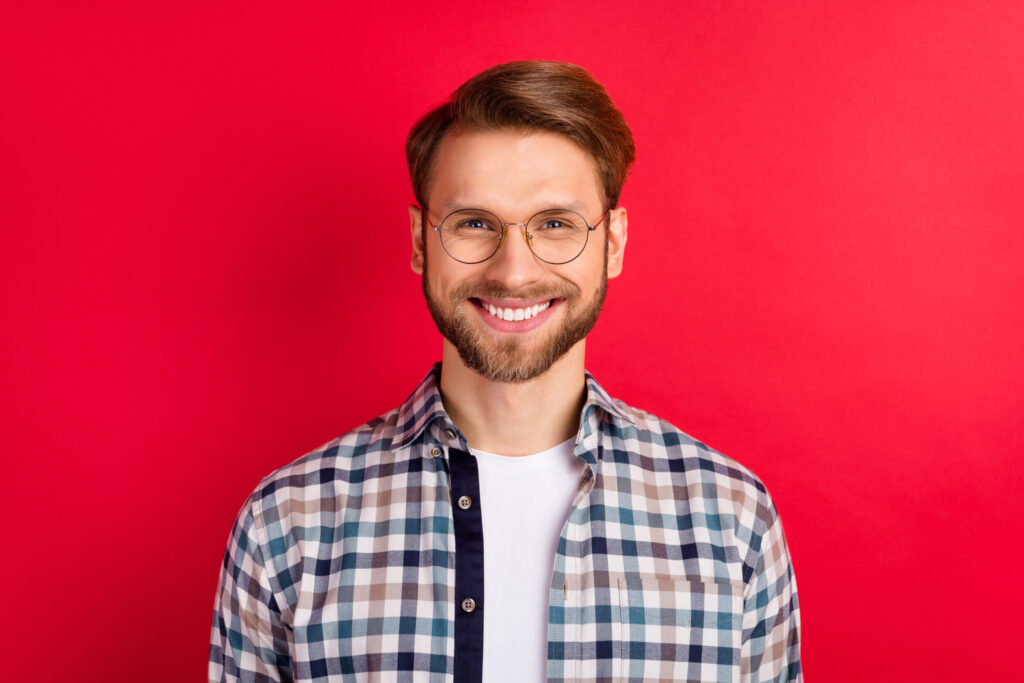 Photo Of Pretty Charming Young Guy Wear Checkered Shirt Glasses Smiling Isolated Red Color Background