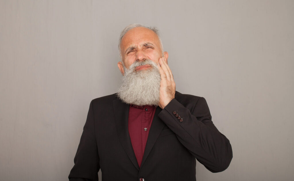 Older Bearded Man Holding Jaw In Pain. He needs tooth fillings.